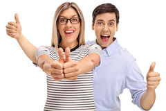 Joyful young man and woman holding their thumbs up Stock Images