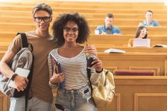 Joyful young man and woman in lecture hall. Lets go home together. Portrait of happy friends embracing while standing in auditory room at university. They are Stock Photo