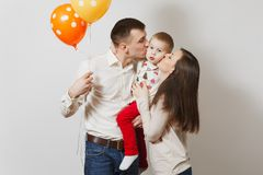 Beautiful European young people on a white background. Emotions, family concept. Joyful young man, women holding, kissing, hugging little cute child boy, air stock photo