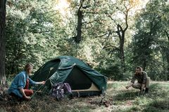 Happy man and woman putting up a tent in forest. Joyful young married couple is pitching a tent together. They are kneeling on grass and laughing Royalty Free Stock Images