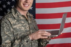 Glad male soldier surfing the internet. Joyful young military man smiling and having device in his hands while typing. Flag on background Royalty Free Stock Photography