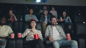Joyful young people watching comedy in cinema laughing looking at screen. Joyful young people men and womena are watching funny comedy in cinema laughing looking stock video