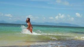Joyful young pretty woman in bikini running into the sea on sunny summer day. slow motion. 1920x1080