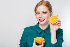 Joyful young redhead woman holding juicy oranges before her eyes. Healthy eating concept. Diet. Isolated over white Royalty Free Stock Image