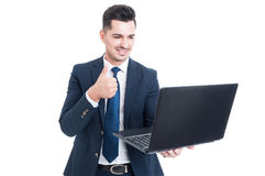 Joyful young salesman holding laptop and thumb up royalty free stock images