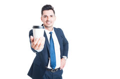Joyful young salesman in suit giving a cup of coffee Royalty Free Stock Photography