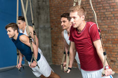 Joyful young sportsmen training in gym. Strong four men are doing push-ups and smiling. They are standing and leaning hands on trx strap Stock Photo