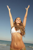 Joyful young woman. Beautiful woman with her arms extended in the air Stock Photography
