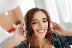 Joyful young woman beaming while listening to music Stock Photos