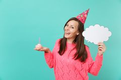 Joyful young woman in birthday hat hold in hand cake with candle empty blank Say cloud, speech bubble for promotional. Content isolated on blue background stock photos
