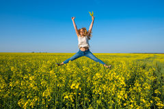 Joyful young woman, blonde jumping and having fun in a field Royalty Free Stock Photo