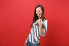 Joyful young woman with closed eyes in striped clothes clenching fist like winner and screaming isolated on bright red. Wall background. People sincere emotions stock images