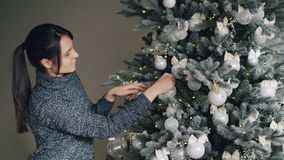 Joyful young woman is decorating New Year tree with stylish silver balls and golden lights enjoying festive activity in stock video