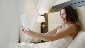 Joyful woman doing a video translation on her tablet pc while lying in bed. Joyful young woman doing a video translation on her tablet pc while lying in bed stock footage