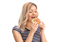 Joyful young woman eating a sandwich Stock Image