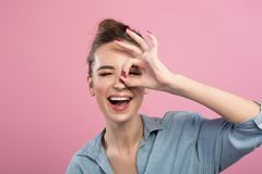 Joyful young woman is expressing delight. Portrait of cheerful girl is standing and looking at camera through hand playfully.  on pink background Stock Photo
