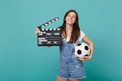 Joyful young woman football fan support favorite team with soccer ball, classic black film making clapperboard isolated stock images