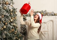 Joyful woman with gift in Santa hat on background of Christmas Stock Photography