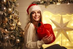 Joyful woman with gift in Santa hat on background of Christmas Royalty Free Stock Photos