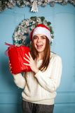 Joyful woman with gift in Santa hat on background of Christmas Royalty Free Stock Photo