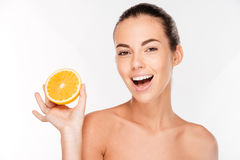 Joyful young woman holding juicy orange Stock Photos