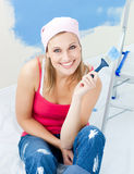 Joyful young woman holding a paint brush smiling. At the camera at home Royalty Free Stock Images