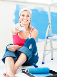 Joyful young woman holding a paint brush smiling. At the camera at home Royalty Free Stock Photo