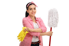 Joyful young woman holding a pair of cleaning gloves and a mop Royalty Free Stock Photography