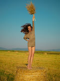 Joyful young woman jumping on hay stack Royalty Free Stock Photo