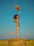 Joyful young woman jumping on hay stack Royalty Free Stock Images