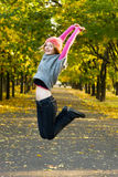Joyful young woman jumping in the park Royalty Free Stock Photography
