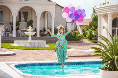 Joyful young woman jumping into the pool while holding a bunch of balloons Royalty Free Stock Photos