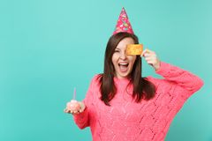 Joyful young woman in knitted pink sweater, birthday hat holding in hand cake with candle, covering eye with credit card. Isolated on blue wall background royalty free stock photo