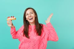 Joyful young woman in knitted pink sweater looking up, spreading hands, holding eclair cake isolated on blue turquoise. Wall background, studio portrait. People royalty free stock image