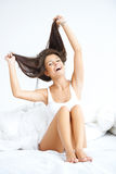 Joyful young woman laughing in bed Stock Photography