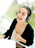 Joyful young woman laughing and listening to music Stock Photo