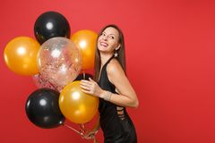 Joyful young woman in little black dress celebrating holding air balloons isolated on red background. St. Valentine`s