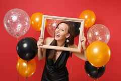 Joyful young woman in little black dress celebrating and holding picture frame on bright red background air balloons
