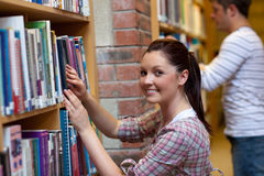Joyful young woman looking for a book Stock Photo