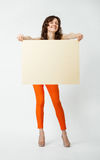Joyful young woman in orange pants holding blank placard. Full length portrait on neutral background Royalty Free Stock Image