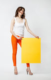 Joyful young woman. In orange pants holding blank yellow paper, full length portrait on neutral background Stock Photo