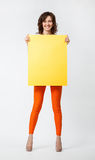 Joyful young woman in orange pants holding blank yellow placard. Full length portrait on neutral background Stock Images