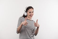 Joyful young woman showing thumb up gesture. Great song. Joyful young woman showing thumb up gestures while enjoying the song Stock Photo