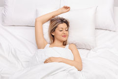 Joyful young woman sleeping on a bed stock image
