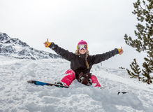 Joyful young woman snowboarder. Sitting in the snow wearing a mask shows a sign on the background of beautiful mountains Royalty Free Stock Photography