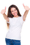Joyful young woman in t-shirt. Showing thumbs up. isolated on white background stock image