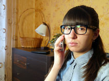 Joyful young woman talking on mobile phone at home Stock Images