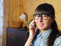 Joyful young woman talking on mobile phone at home Stock Photos
