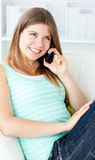 Joyful young woman talking on phone on the sofa Stock Images