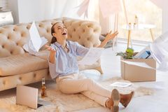 Joyful young woman throwing the documents and smiling. Extremely happy. Emotional beautiful joyful woman looking happy to get a new job while sitting on the Royalty Free Stock Photos